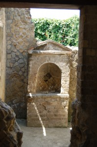 Shrine to the Lares in Herculaneum. The Lares were the guardian spirits of each Roman home and family. But individual districts within towns had their own Lares too.  Image by Natasha Sheldon, all rights reserved.